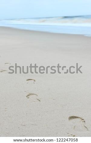 Footprints on a sandy beach - stock photo
