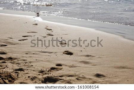 Footprints on an empty beach at sunset - stock photo