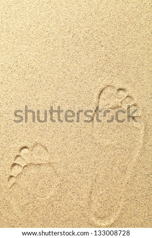 Footprints on beach background with copy space. Sand texture
