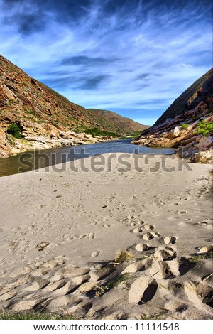 Footprints on beach next to awesome river in mountains. Shot in the Langeberge highlands near Grootrivier and Gouritsrivier rivers crossing, Garden Route, Western Cape, South Africa. - stock photo
