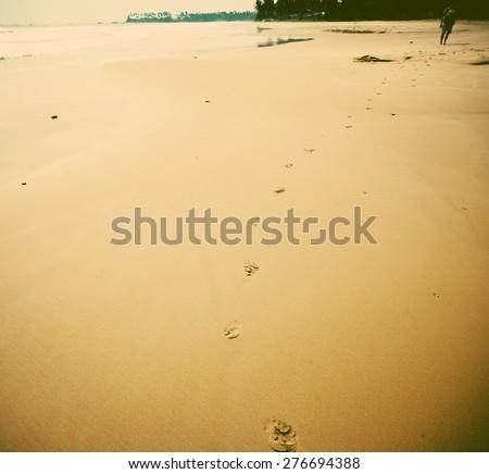 Footprints on beach - retro style background - stock photo