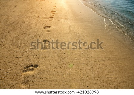 Footprints on sand along sea shore and golden sunset