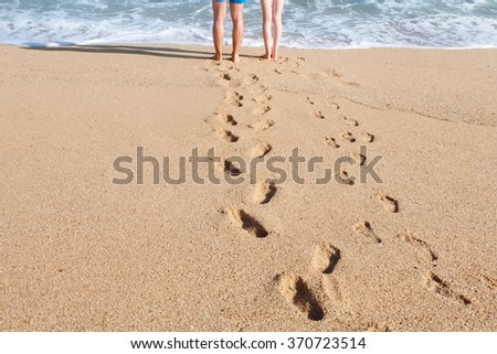 Footprints on sand from legs of young couple standing near sea water  - stock photo