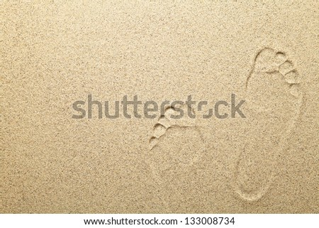 Footprints on sandy beach background with copy space - stock photo
