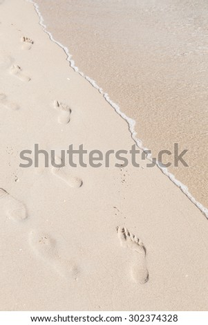 Footprints on the beach. Footsteps of people walking on the beach by the sea. - stock photo