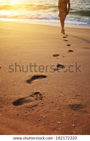Footprints on the beach sand.Traces on the beach. Footsteps on the beach by the sea in summer  - stock photo