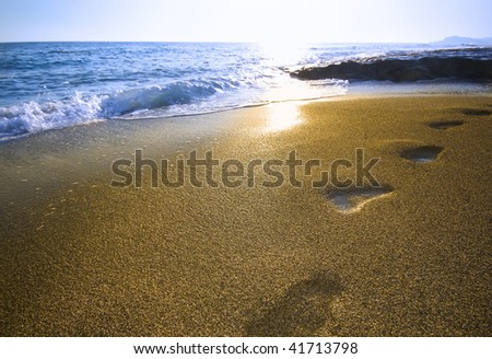 footprints on the beach surf and sunset - stock photo
