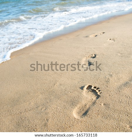Footprints on the sand beach - stock photo