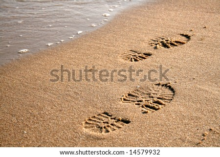 Footprints on the sand near the waves