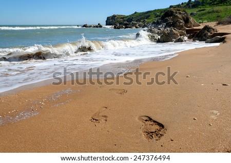 Footprints on the wet sand on the Black Sea - stock photo
