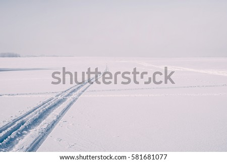 Footprints on white snow as straight lines - trails, disappearing into the distance. Winter sports.
