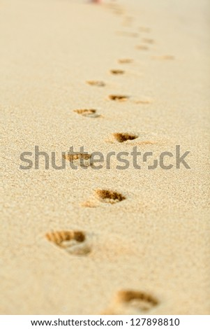 Footprints on yellow sand on the seashore