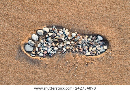 Footstep with small pebbles on the sandy beach - stock photo