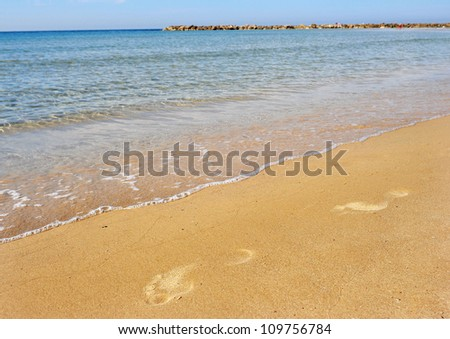 Footsteps along the beach. concept photo of travel, vacation and freedom  - stock photo