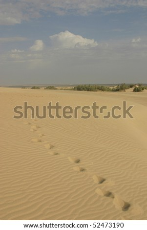 Footsteps in Sahara desert and blue sky with some clouds in background.