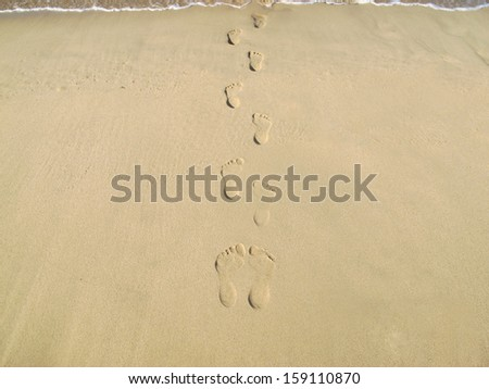 footsteps on the beach at sunset time - stock photo