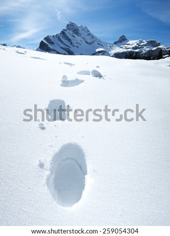 Footsteps on the snow. Swiss Alps - stock photo