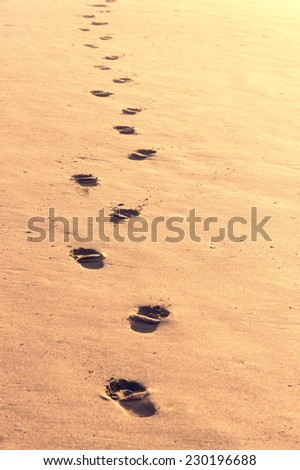 footsteps track in the sand - stock photo