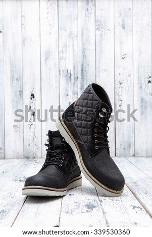Footwear concept. Men's winter leather boots of black color are nice idea for active holidays isolated on white wooden background.  - stock photo