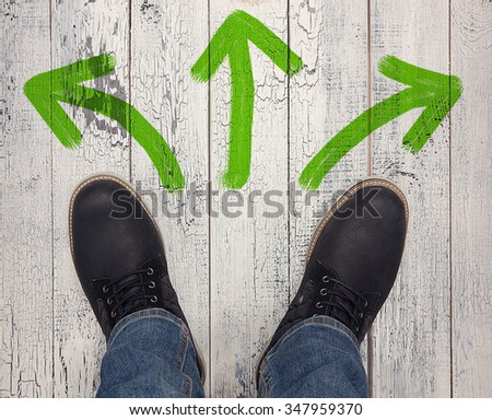 Footwear concept. Top view of men's winter boots of black colour. Man making photo of his fashionable boots isolated on wooden.  - stock photo