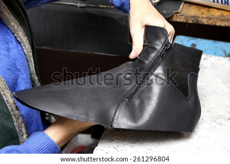 Footwear production by human hands in a shoe factory. - stock photo
