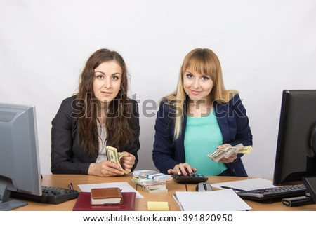 for office table two girls employee count money - stock photo
