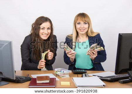 for office table two women collaborators happily hold hands in a pack with the money and express a strong admiration - stock photo