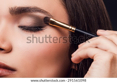 For perfect glance. Close-up of young woman applying eye shadow while standing against black background - stock photo