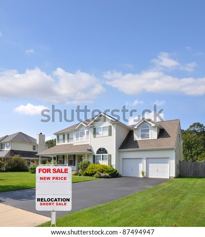 For Sale Real Estate Sign at Driveway Edge of Two Car Garage Suburban Home in Residential District Blue Sky with Clouds Day