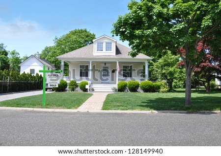 For Sale Sign Front Yard Lawn of Suburban Bungalow Home in Residential Neighborhood - stock photo