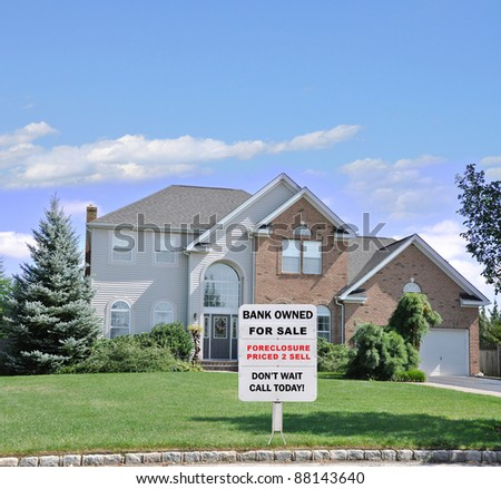 For Sale Sign on Front Yard Lawn of Landscaped Suburban Brick McMansion Home in Residential Neighborhood - stock photo
