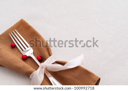 For the Thanksgiving or Christmas Table, Antique Silver Ware, Brown Napkin, Tied with a Satin Ribbon, and Ornaments against a White Background, a Table Cloth with Room for Text or Copy - stock photo