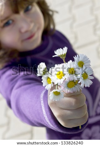 For You Mom. Young daughter gives fresh picked spring daisies bouquet - stock photo