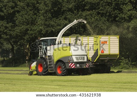 forage harvester and transport of grass with tractor and a loader wagon - stock photo