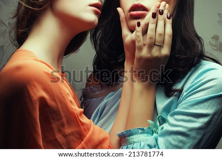 Forbidden love concept. Portrait of two gorgeous girlfriends in blue and orange retro dresses making love in hotel room. Tender violence. Passion and kisses. Vintage, vogue style. Studio shot - stock photo