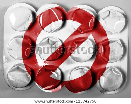Forbidden sign painted on painted on tablets or pills - stock photo