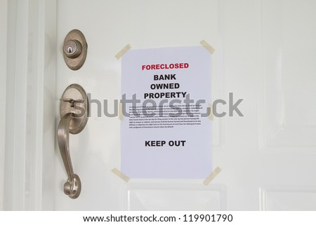 Foreclosed notice on a main door of a house - stock photo