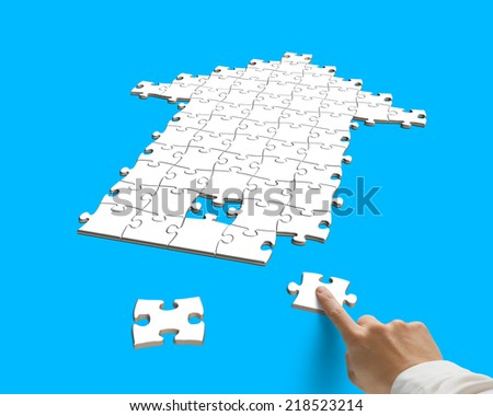 forefinger with puzzles in arrow shape isolated on blue - stock photo