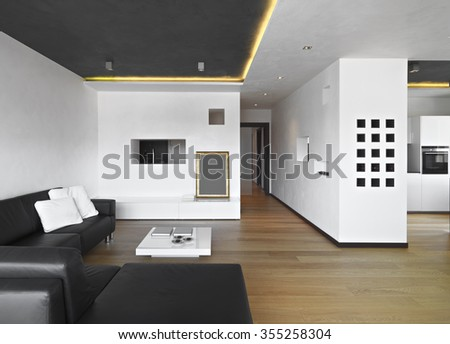 foreground of a living room with leather sofa, wood floor, overlooking on the kitchen - stock photo
