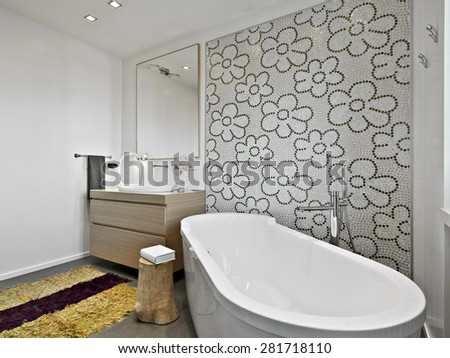 foreground of bathtub overlooking on wood furniture for a washbasin in a modern bathroom with mosaic wall and yellow carpet - stock photo