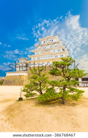 Foreground trees inside the keep of courtyard at base of the stronghold of Himeji-jo castle on a clear sunny day in Himeji, Japan after early 2015 renovations. Vertical