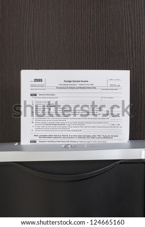 Foreign Earned Income form in shredder with wooden desk in background - stock photo