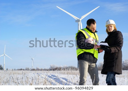 Foreman and engineer in snow winter field with wind turbines in background