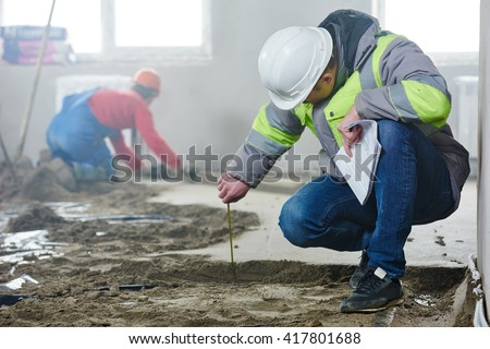 foreman builder inspecting concrete construction work in apartment - stock photo