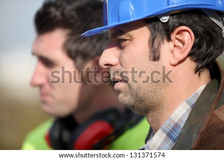 Foreman chatting to colleague - stock photo