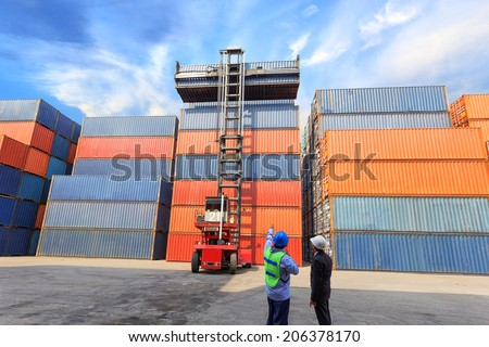 foreman control forklift handling follow order from his manager for move the container box loading at dock yard - stock photo