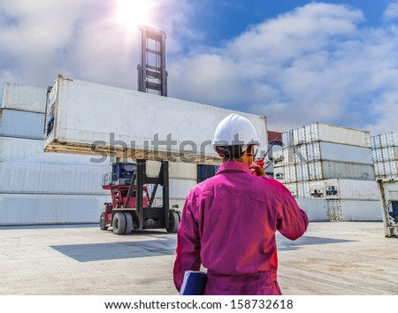 foreman control forklift handling the container box load to big truck selective focust at container box. - stock photo