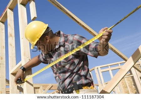Foreman examining framework with measure tape at construction site - stock photo
