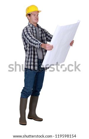 Foreman examining plans - stock photo