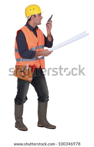 Foreman giving instruction via radio - stock photo